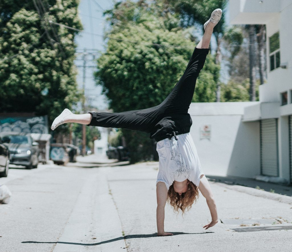 girl doing cartwheel, on road